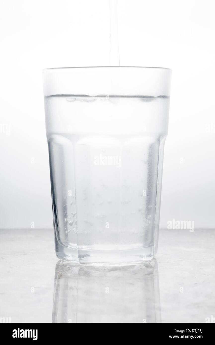 Glas Wasser mit Gießen Stockbild