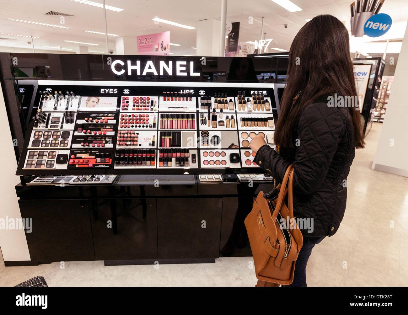 Eine junge Frau einkaufen und kaufen Chanel Kosmetik, Stiefel, Cambridge UK Stockbild