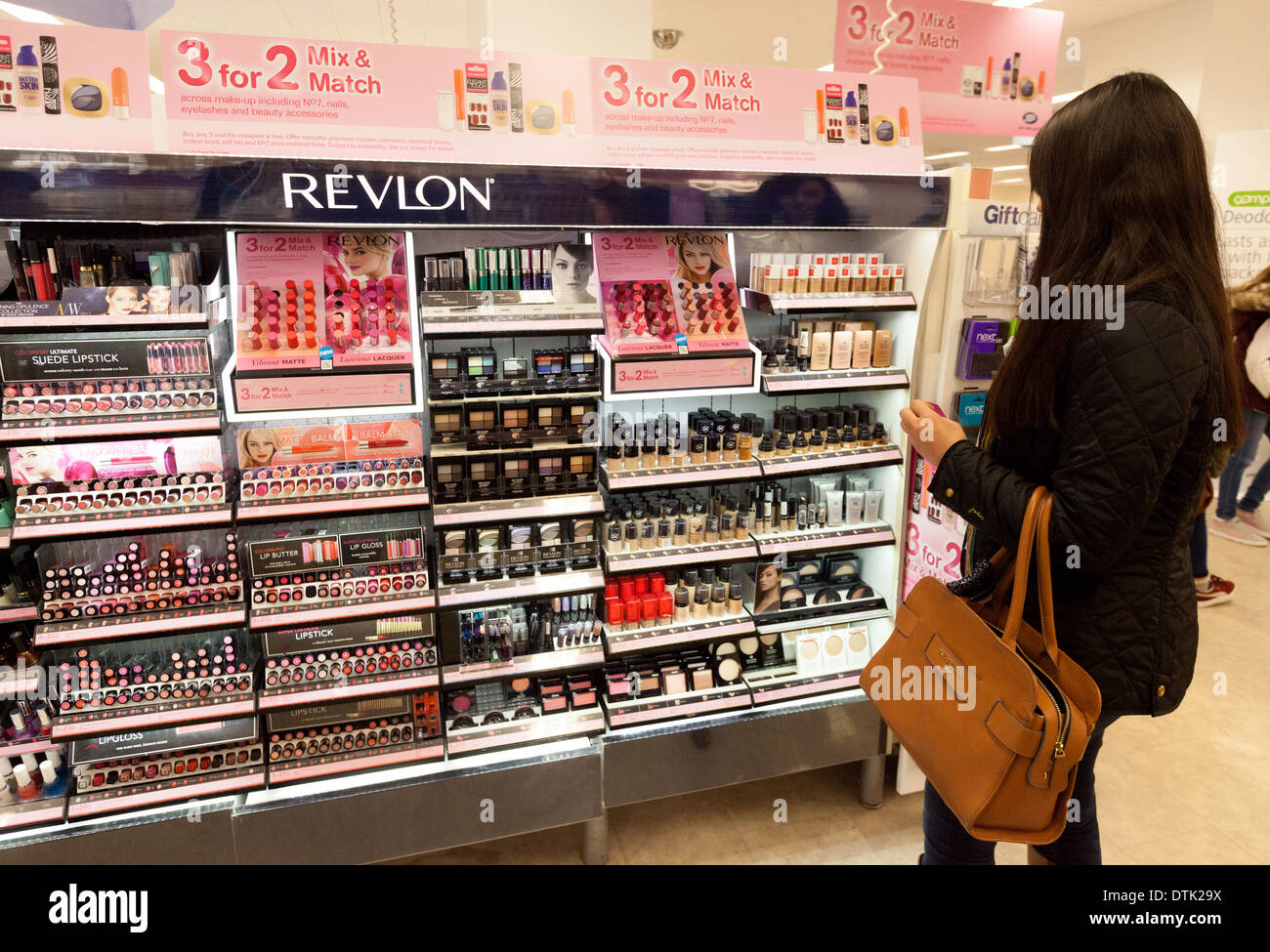 Eine junge Frau für Einkaufs- und Kauf von Revlon Kosmetik, Stiefel, Cambridge UK Stockbild