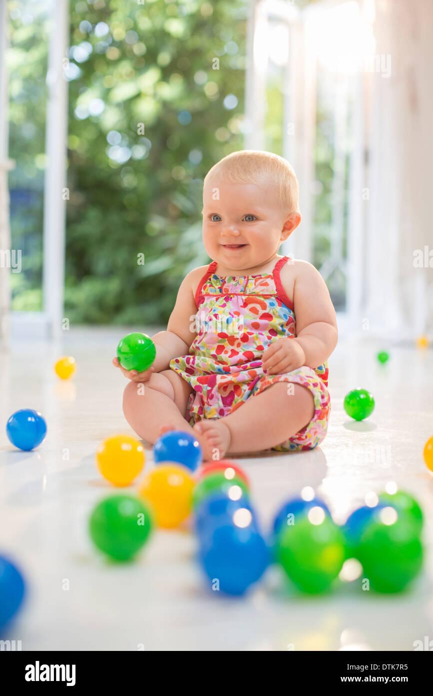 Babymädchen spielen mit Spielzeug auf Etage Stockbild