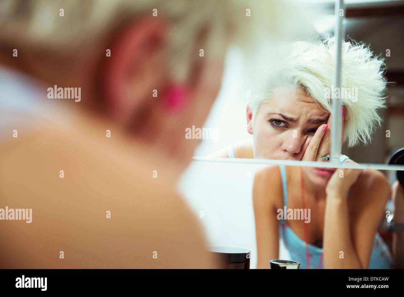 Verkatert Frau prüft sich selbst im Spiegel Stockbild