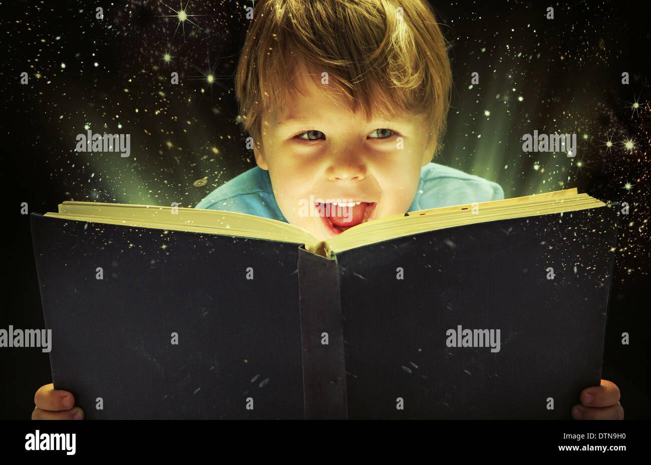 Kleiner Junge mit einem alten Zauberbuch Stockbild