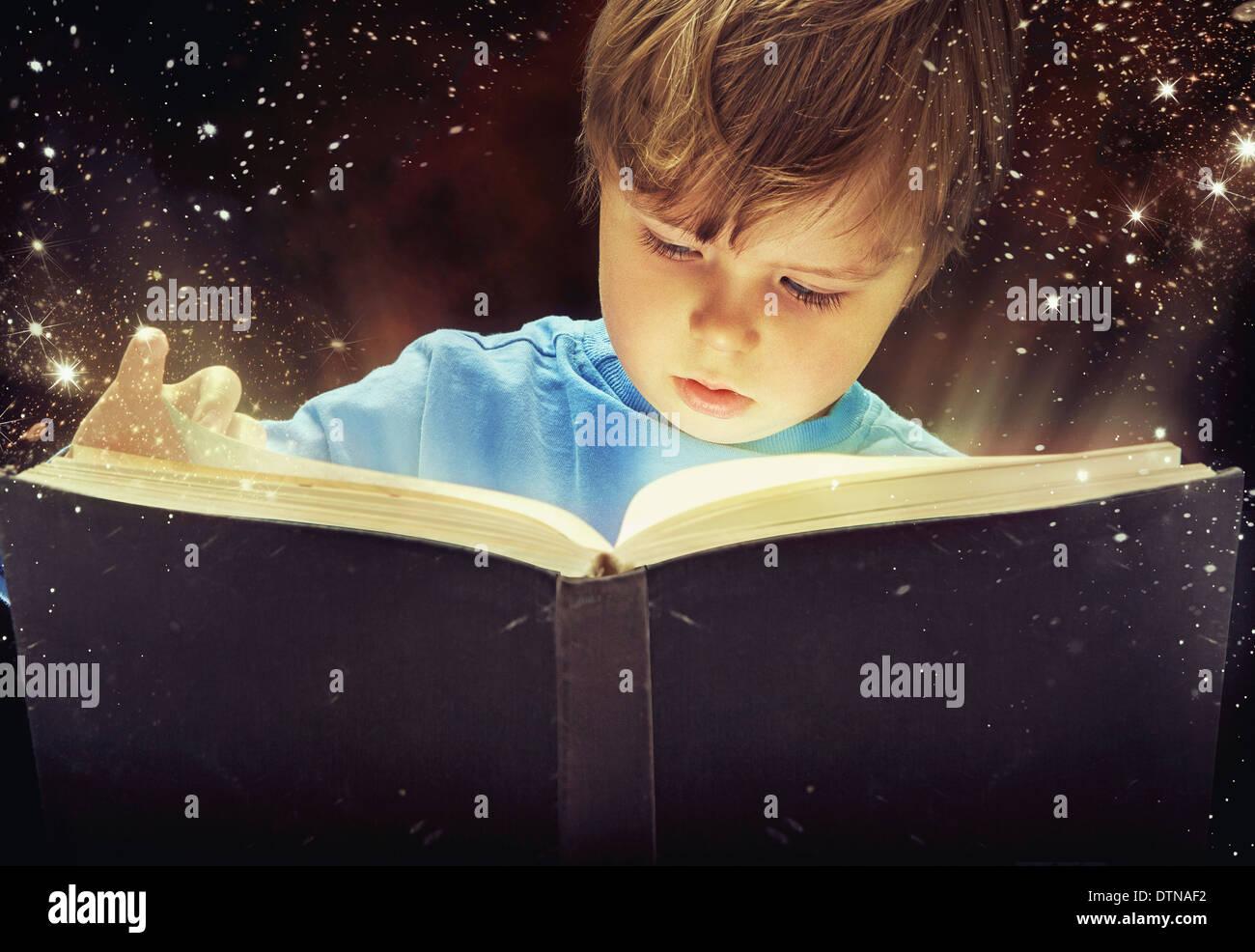 Kleiner Junge mit dem magischen Buch erstaunt Stockbild