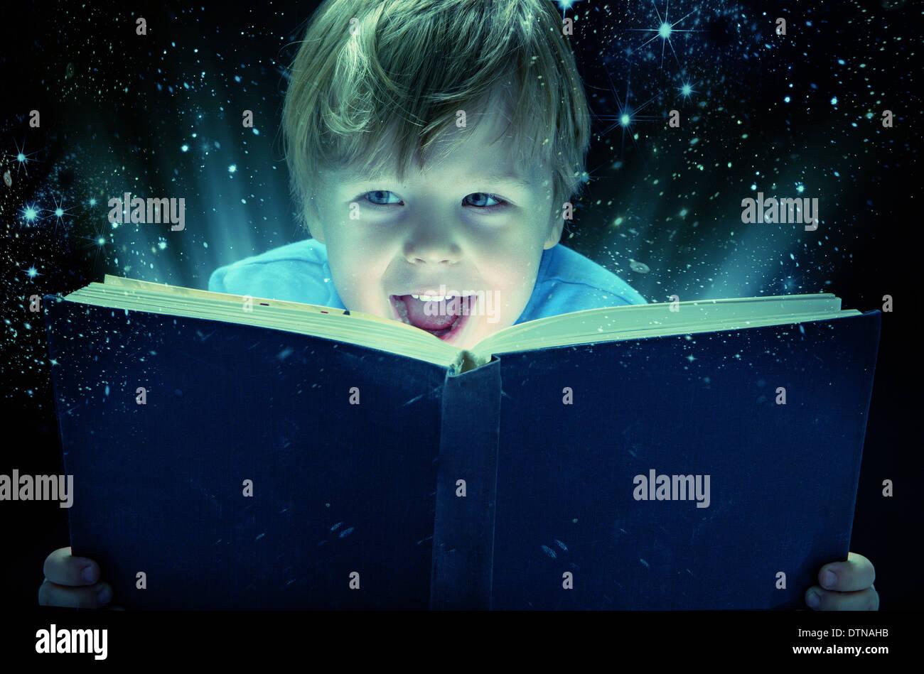 Kleinen junge mit alten Zauberbuch lachen Stockfoto