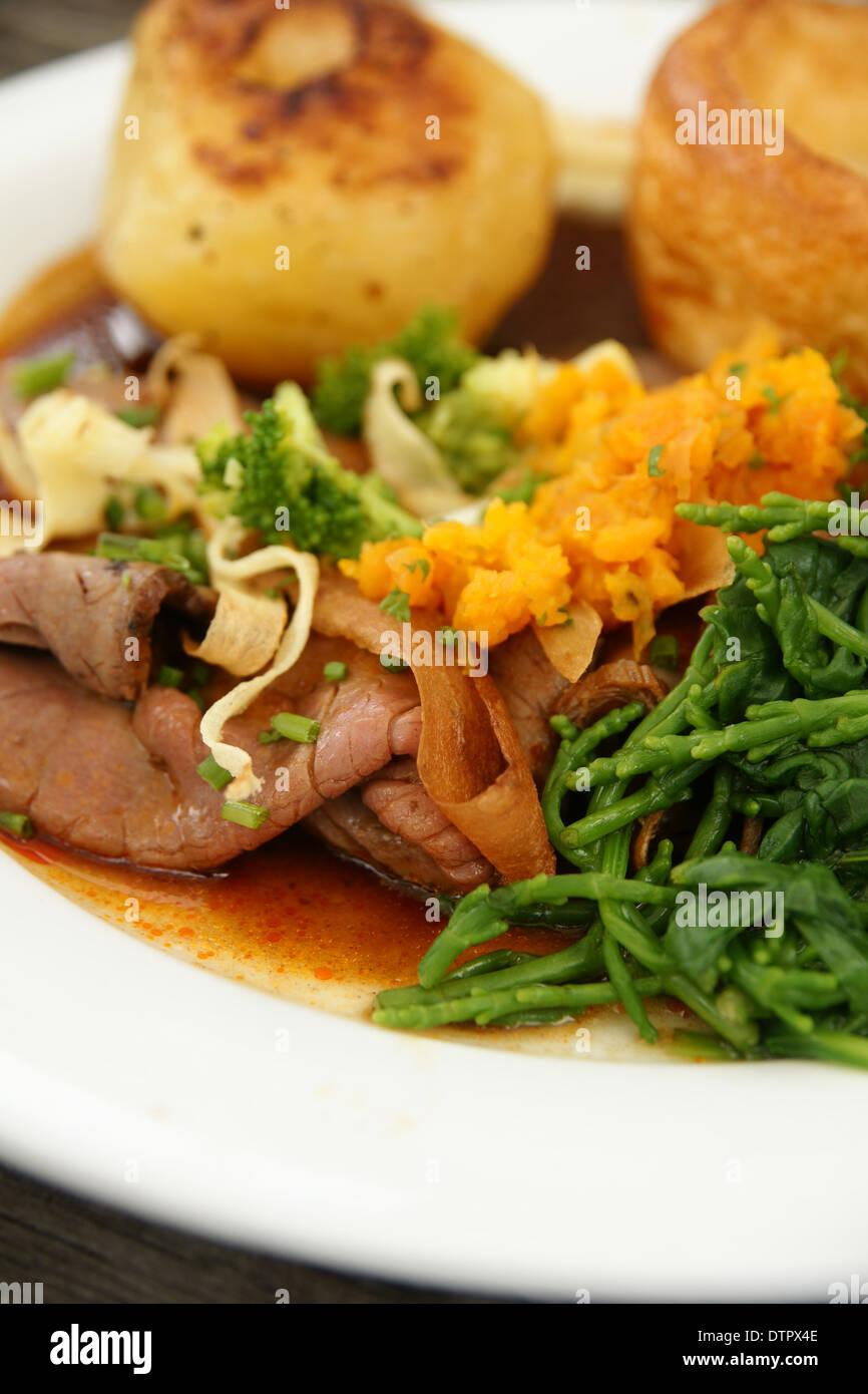 Gebratenes Rindfleisch Abendessen mit Bratkartoffeln, Yorkshire Pudding und Gemüse püriert Schwede und Queller Stockbild