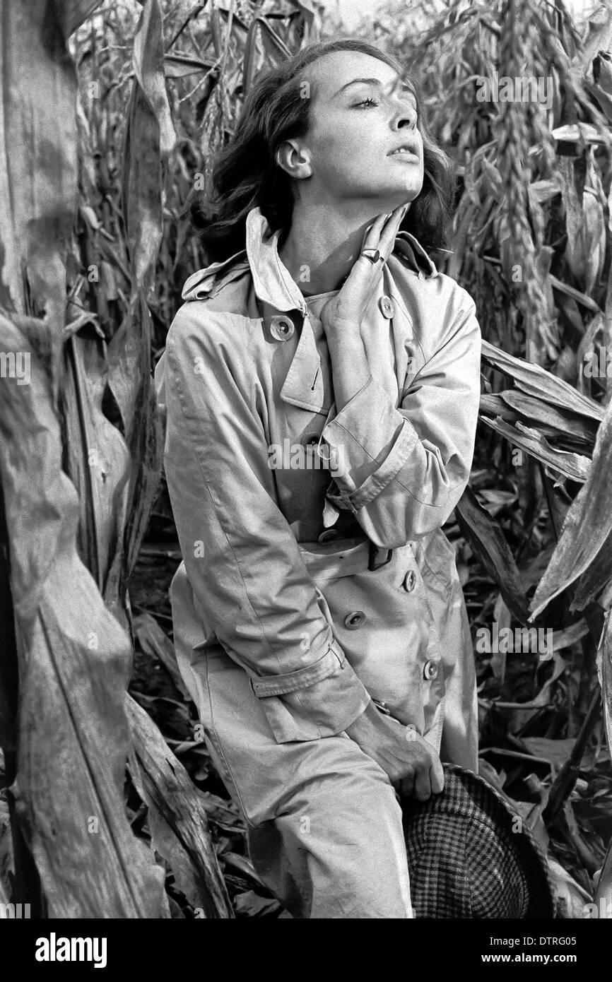 60er Jahre Mode Modell Mit Regenmantel Posiert In Einem Maisfeld