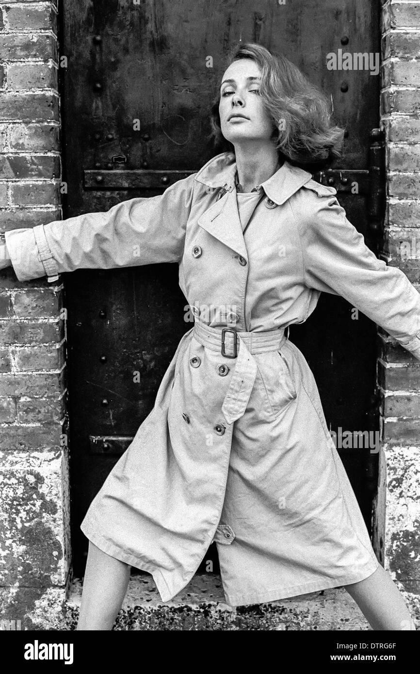 60er Jahre Mode Modell Mit Regenmantel Posiert Vor Einem Schwarzen
