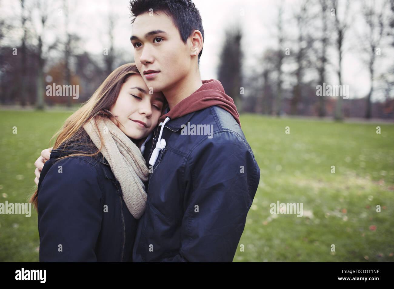 Liebevolle Teenager-paar umarmt im Freien. Junger Mann und Frau in der Liebe im Park. Exemplar. Stockbild
