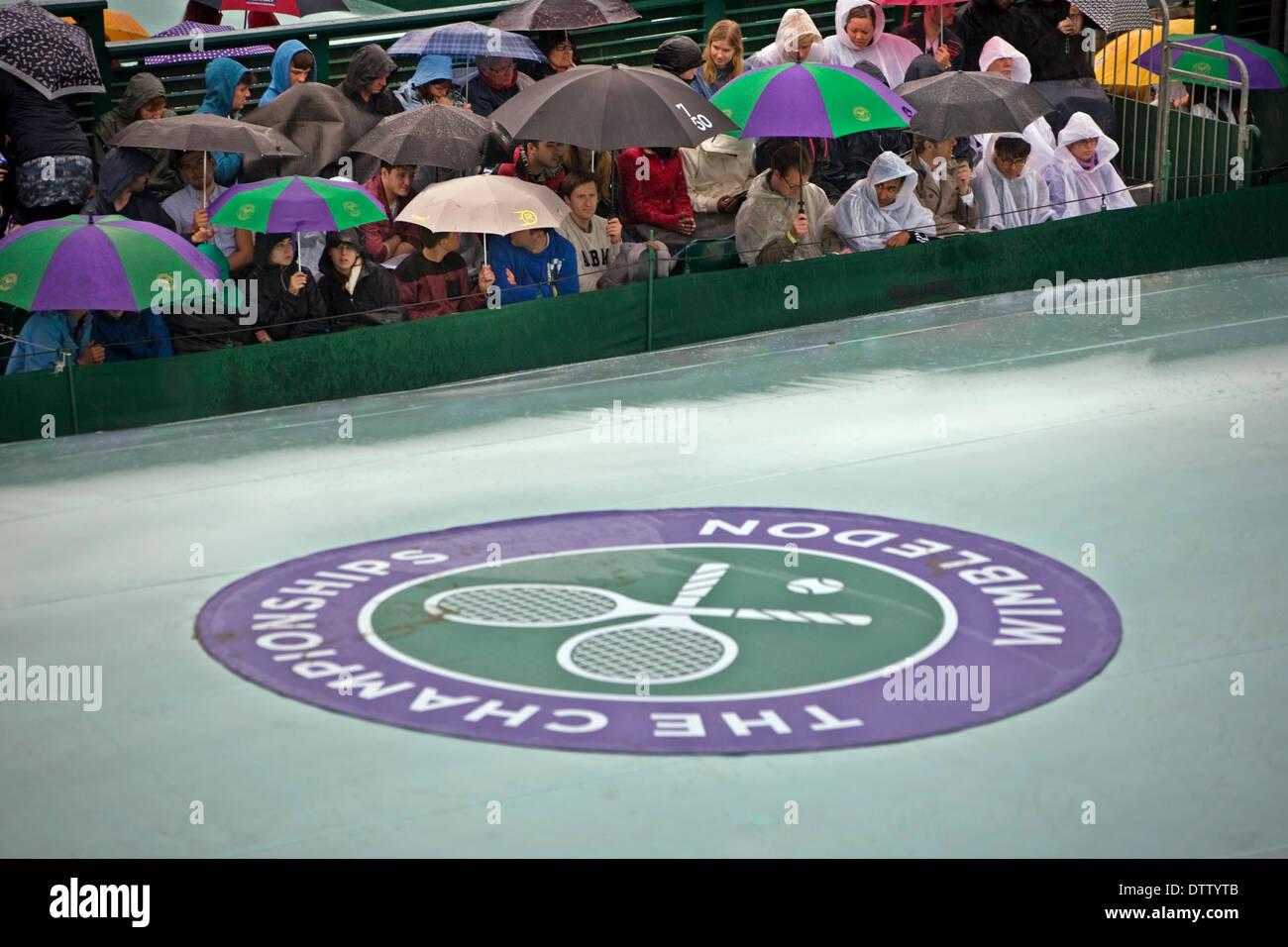 Regen Sie an Wimbledon Gericht Abdeckung auf Schirm oben Menschenmenge wartete für das Spiel Stockbild