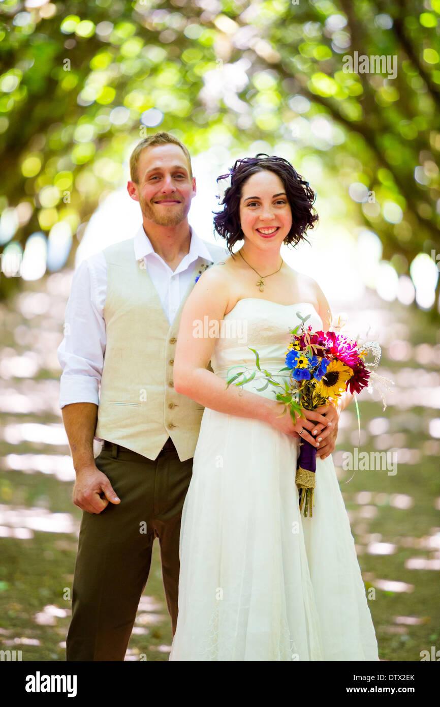 Braut und Bräutigam posieren für ein Porträt in einem hinterleuchteten Obstgarten am Tag ihrer Hochzeit in Oregon mit Licht, das durch die Bäume. Stockbild