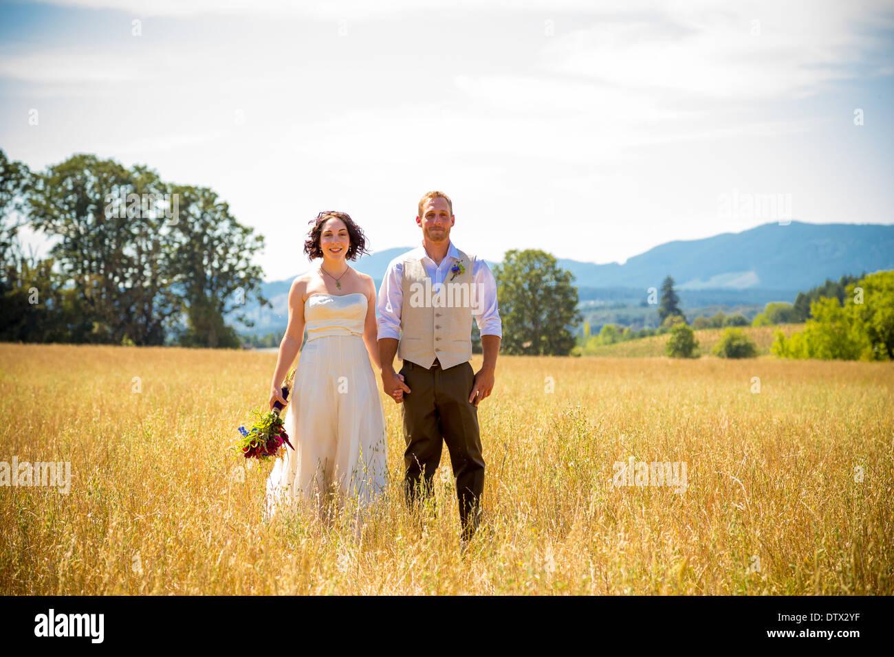Braut und Bräutigam am Tag ihrer Hochzeit zusammen in einem Feld stehen. Stockbild