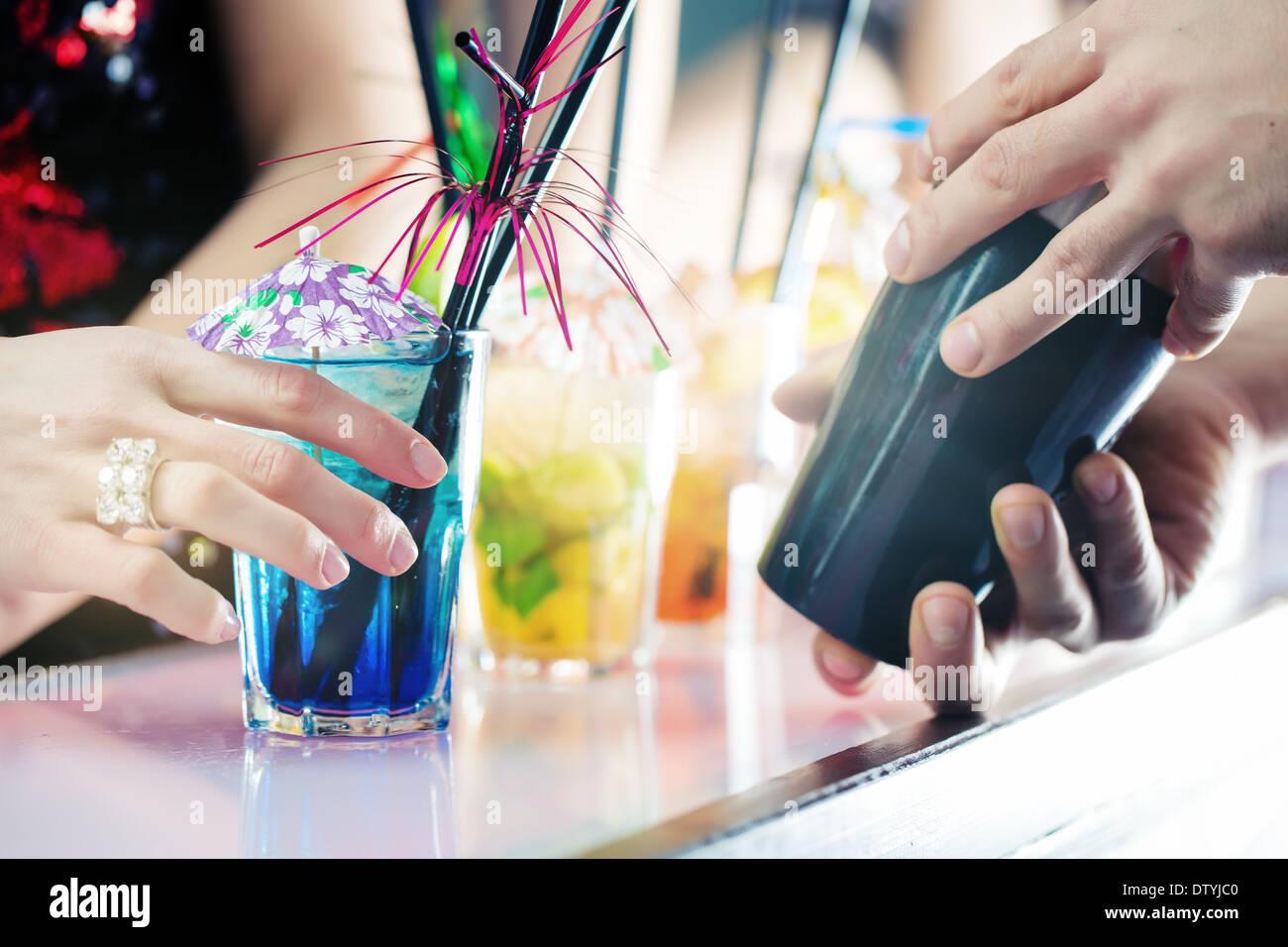 Party People in bar zu feiern, Spaß mit Getränken und ein Barkeeper Gruppe Stockbild