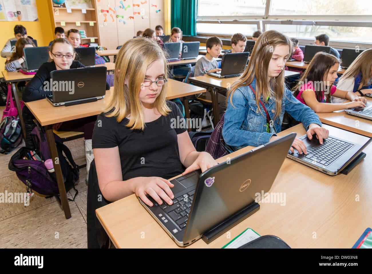 Junior High School Schüler (ca. 12 Jahre alt) arbeiten mit ihren Laptops in ihrem Klassenzimmer. Stockfoto