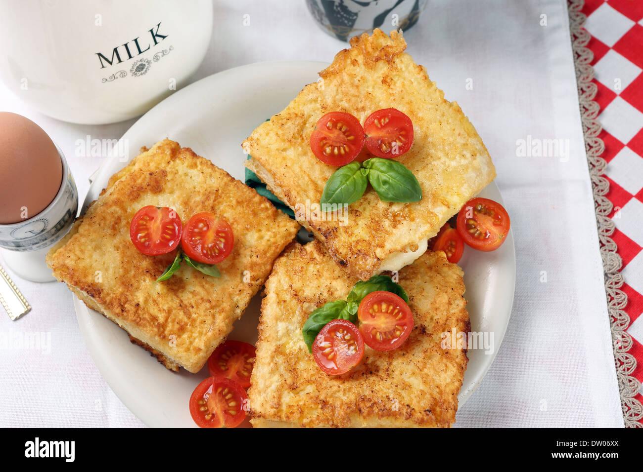 Toast mit Käse und Tomaten, serviert mit Spiegelei und eine Tasse Milch Stockbild