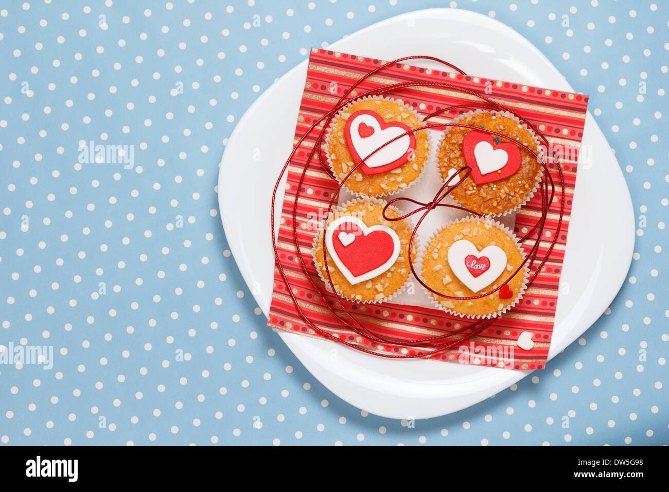 dcd2bab5ab7bee weißen Teller mit Valentinstag-Muffins mit roten und weißen Herzen auf eine  blaue im Hintergrund