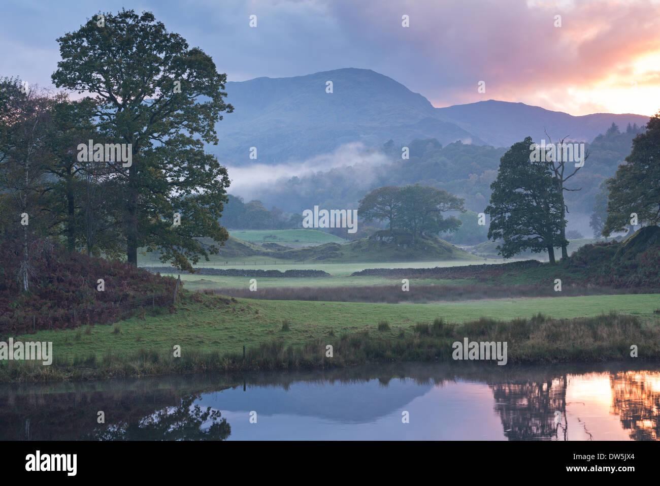Atmosphärischen Sonnenuntergang aus dem Fluß Brathay in der Nähe von Elterwater, Lake District, Cumbria, England. Herbst (Oktober) 2013. Stockbild