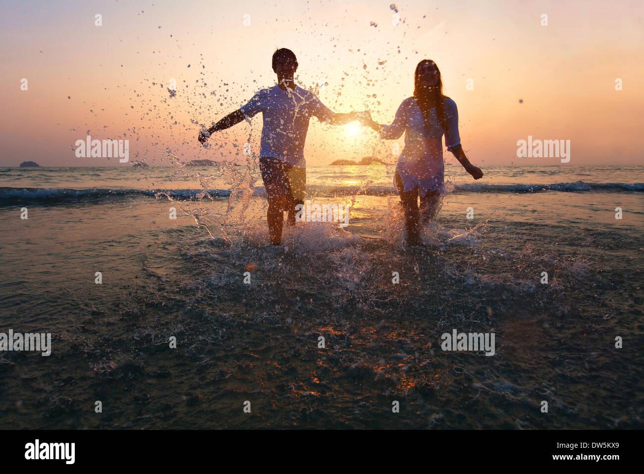 glückliches Paar Sonnenuntergang am Strand genießen Stockbild