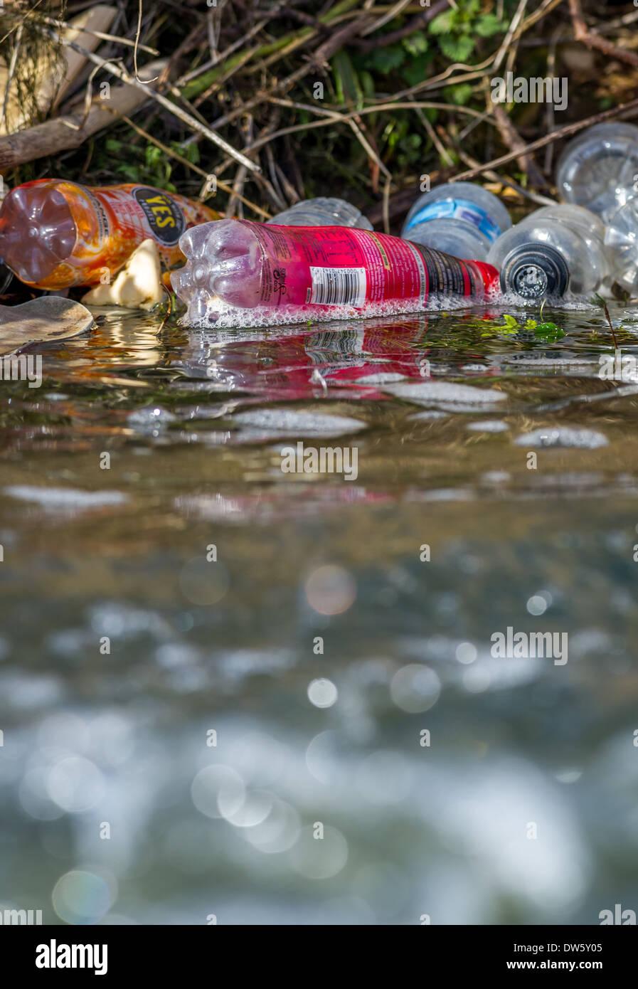 Ausrangierte Plastikflaschen verschmutzen das Ufer eines Flusses. Stockbild