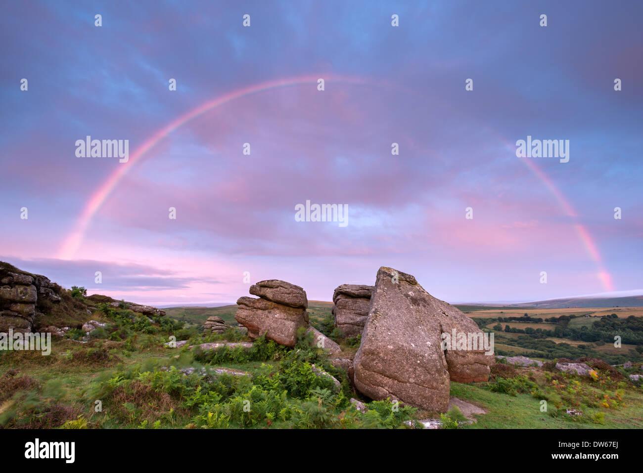 Regenbogen über Holwell Tor bei Sonnenaufgang, Dartmoor, Devon, England. (August) im Sommer 2013. Stockbild