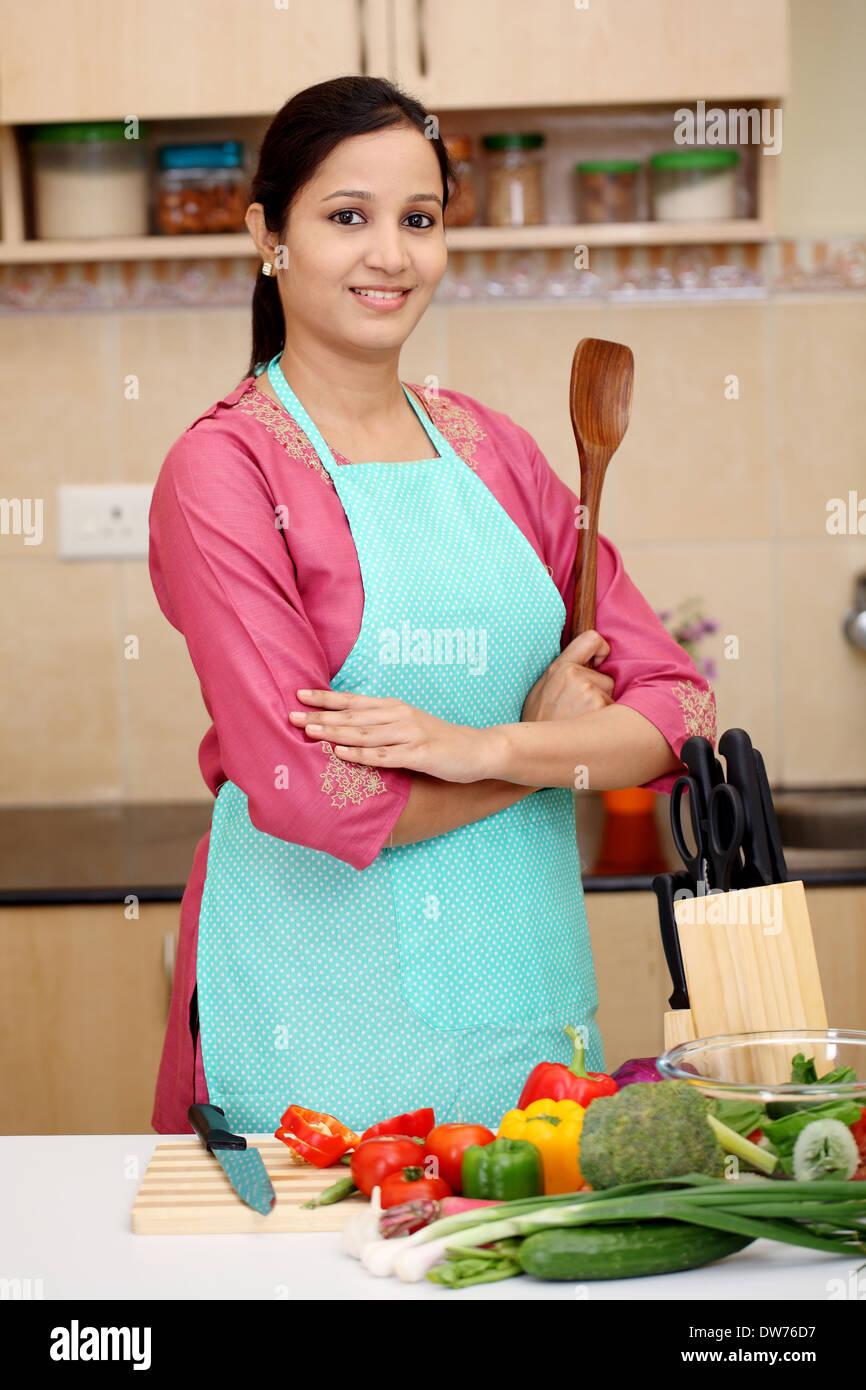 Selbstbewusste junge indische Frau mit Küchengerät Stockbild