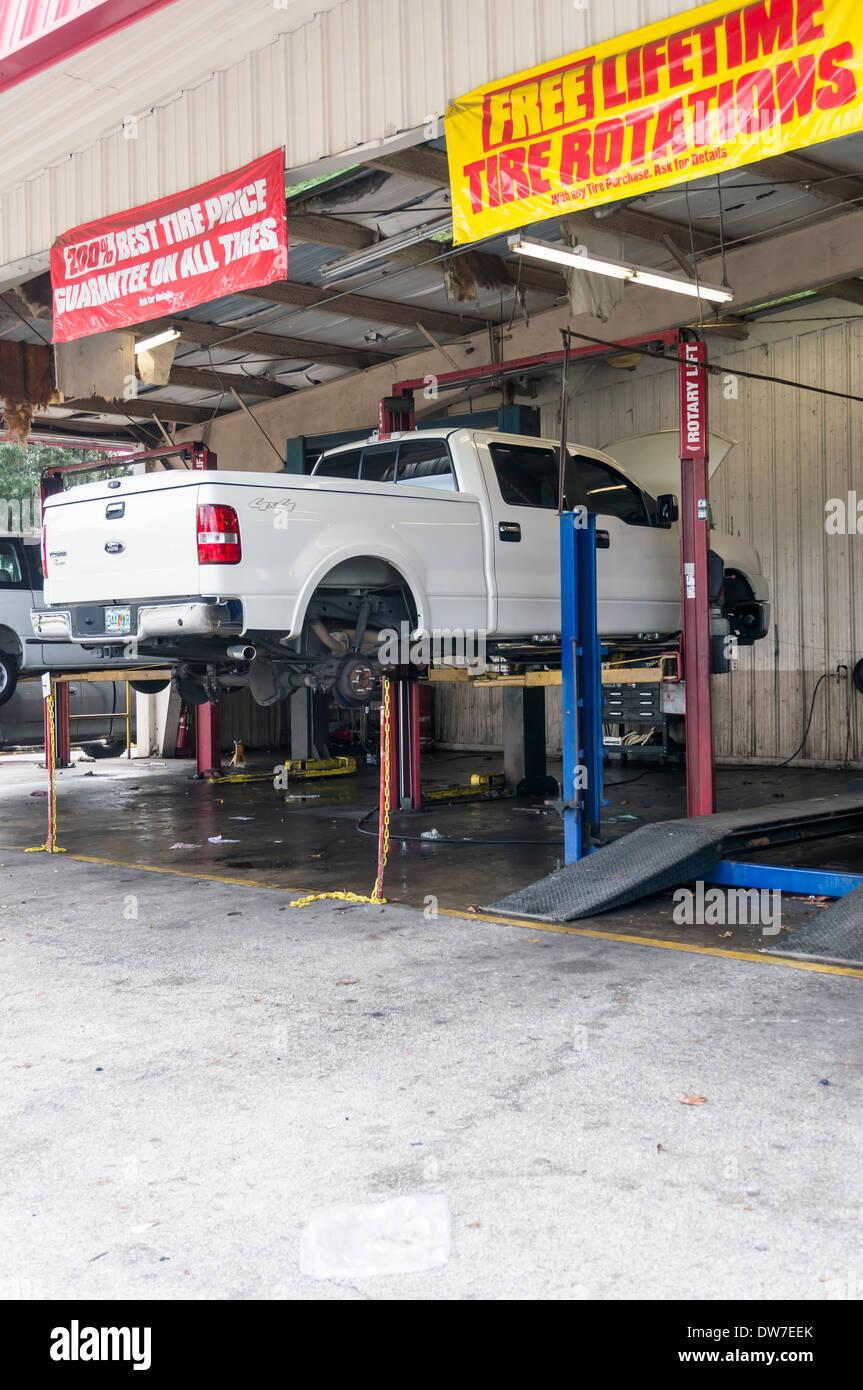 Weiß extended Cab Pickup ohne Reifen auf einer Hebebühne in Mechanik Garage. Banner für Reifen Vertrieb und Drehung hängen. Stockbild