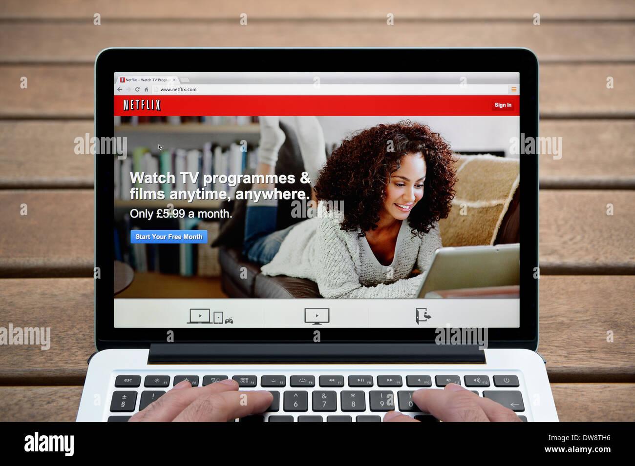 Der Netflix-Website auf einem MacBook Hintergrund eine Holzbank im Freien einschließlich eines Mannes Finger (nur zur redaktionellen Verwendung). Stockbild