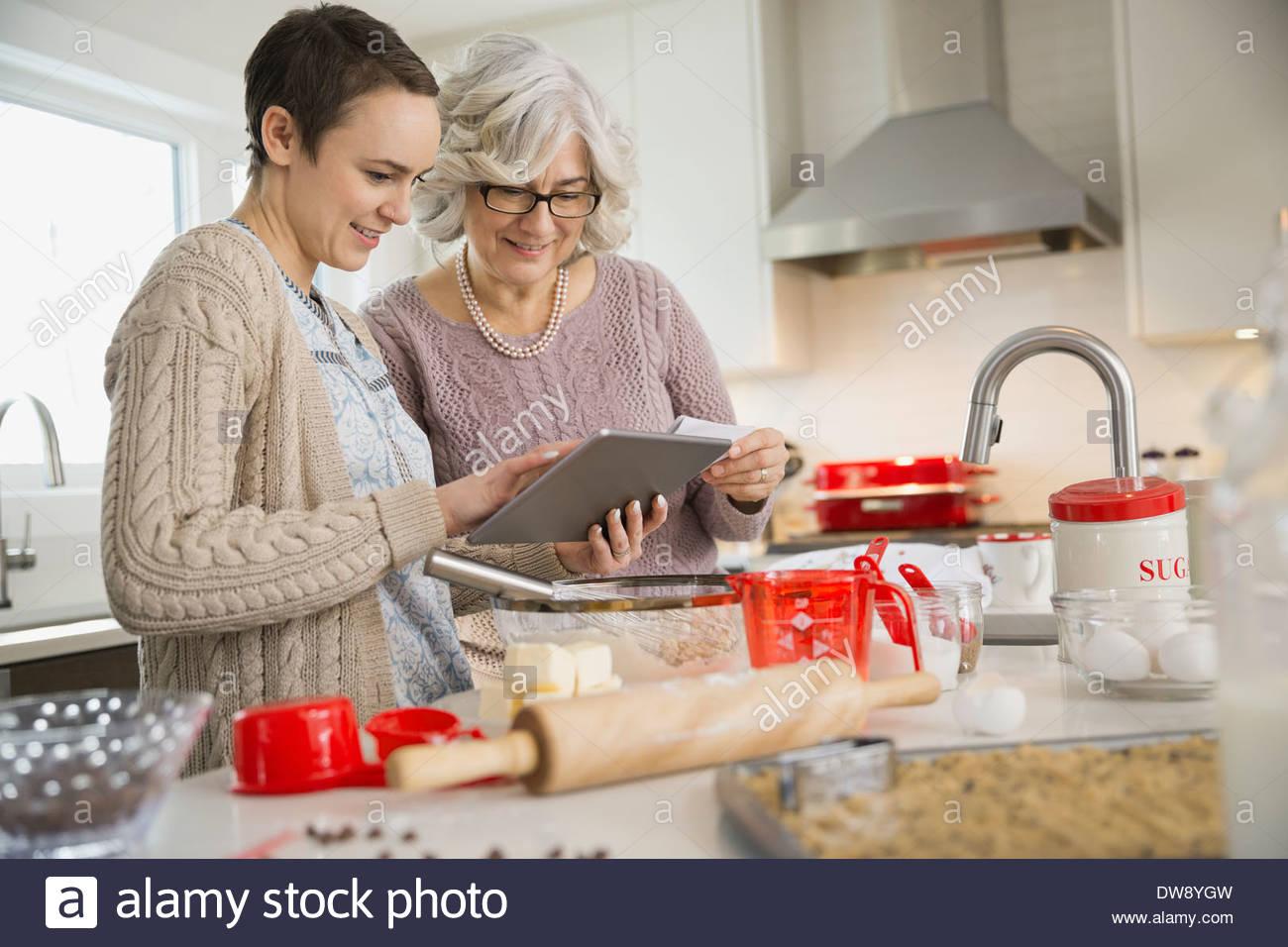Mutter und Tochter betrachten Rezepte auf digital-Tablette Stockbild