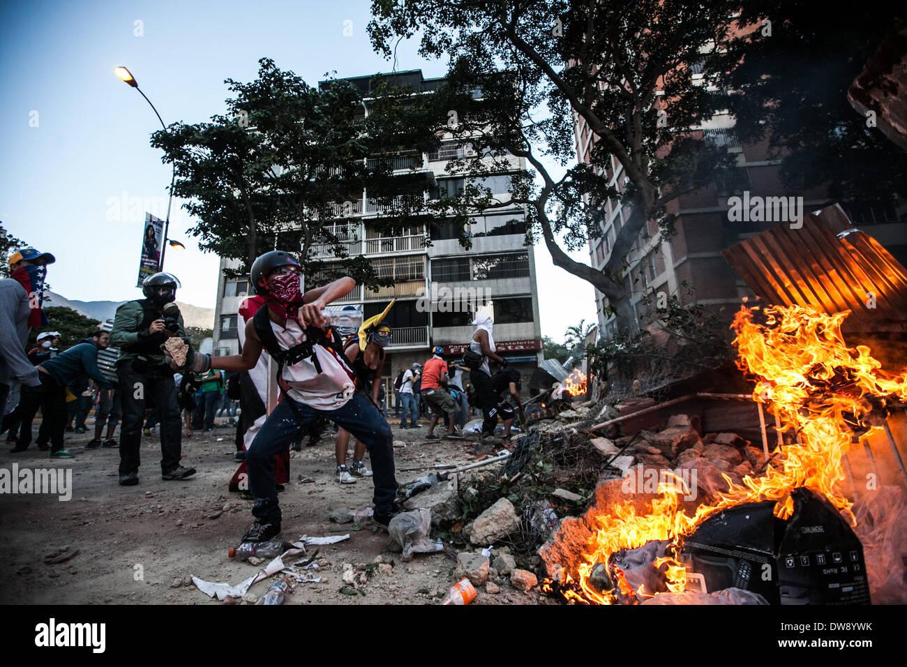 Caracas, Venezuela. 3. März 2014. Demonstranten werfen Felsen in einem Kampf gegen die bolivianische Polizei Stockbild