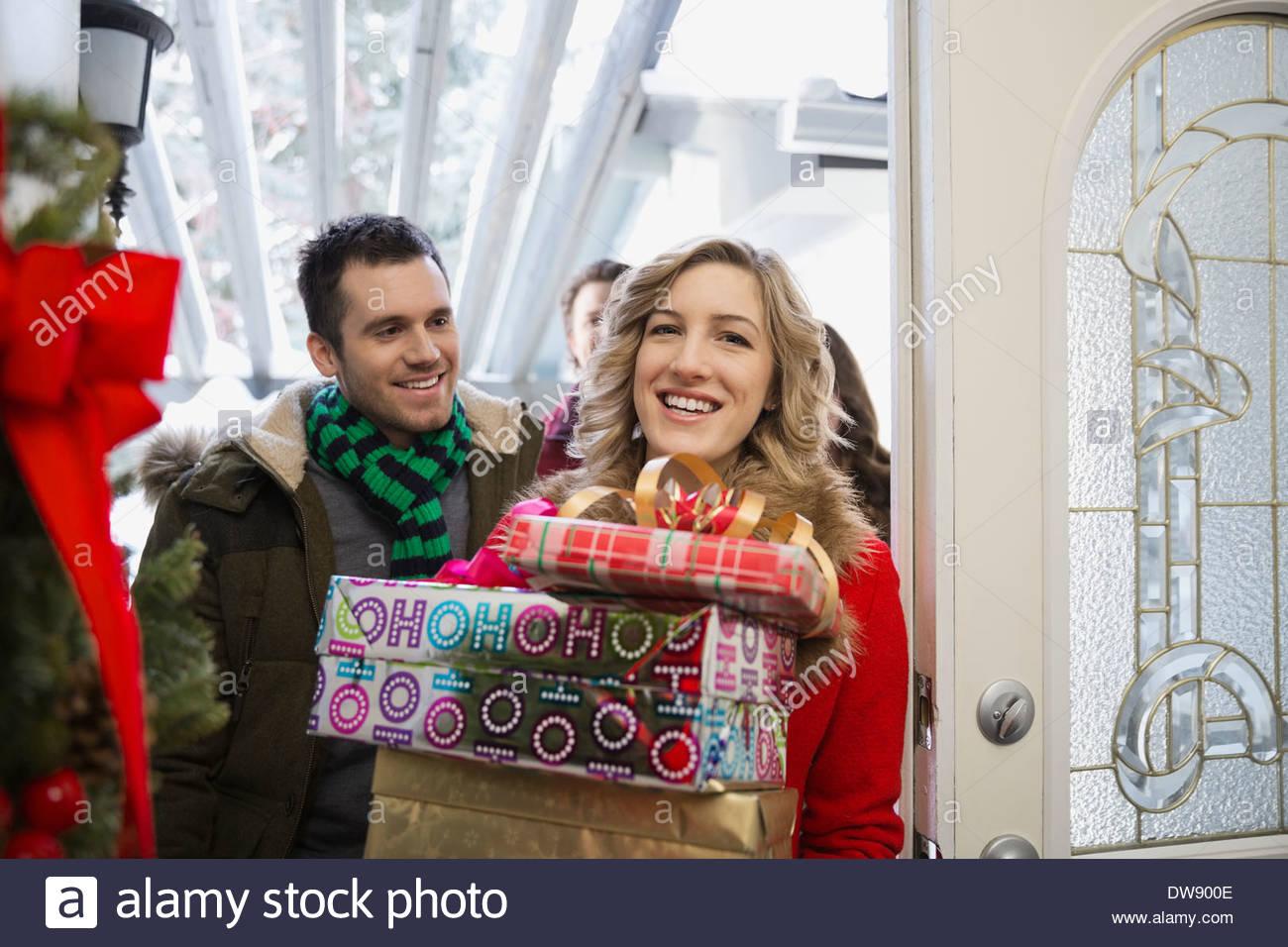 Freunde mit Stapel der Weihnachtsgeschenke zu Hause ankommen ...