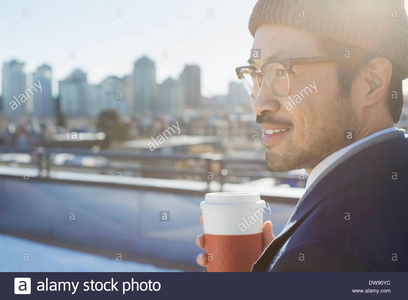 Nachdenklicher Mann halten Einweg-Tasse auf Terrasse Stockbild