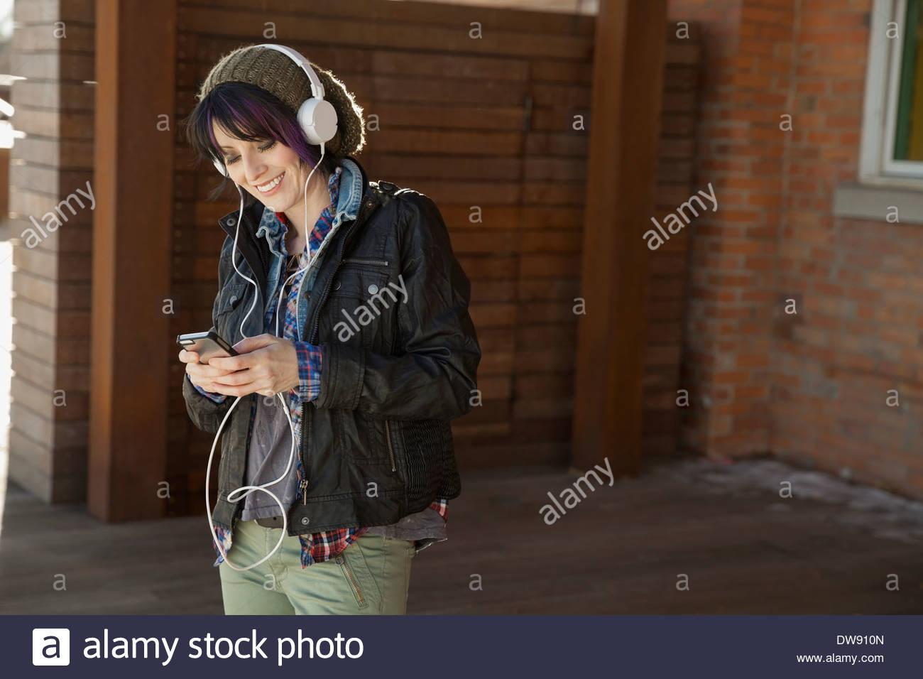 Lächelnde Frau anhören von Musik über Kopfhörer im freien Stockbild