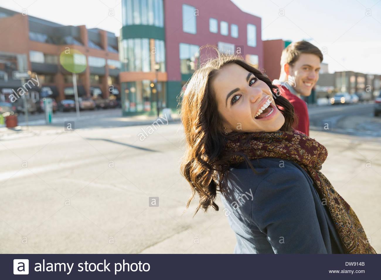 Fröhliche Frau, die im Rückblick auf Stadtstraße Stockbild