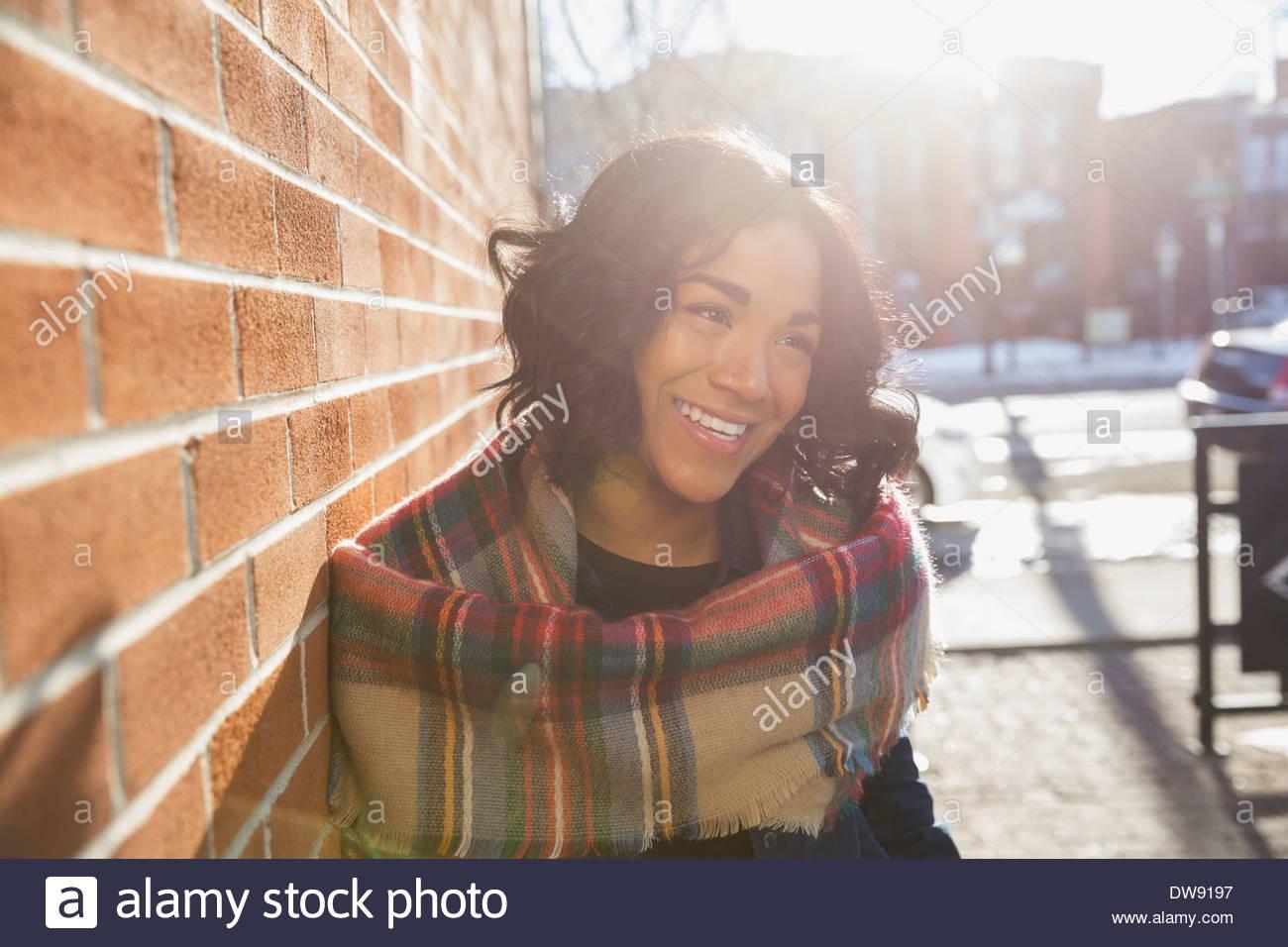 Lächelnde Frau, die durch Mauer Stockbild