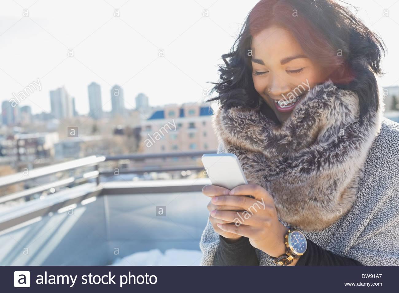 Frau in gemütliche Schal mit Smartphone im freien Stockbild