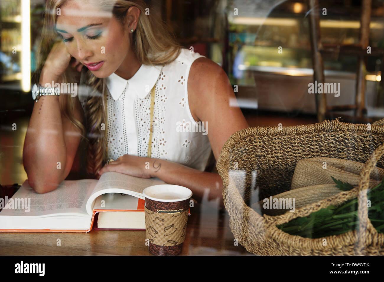 Junge Frau im Café lesen Stockbild