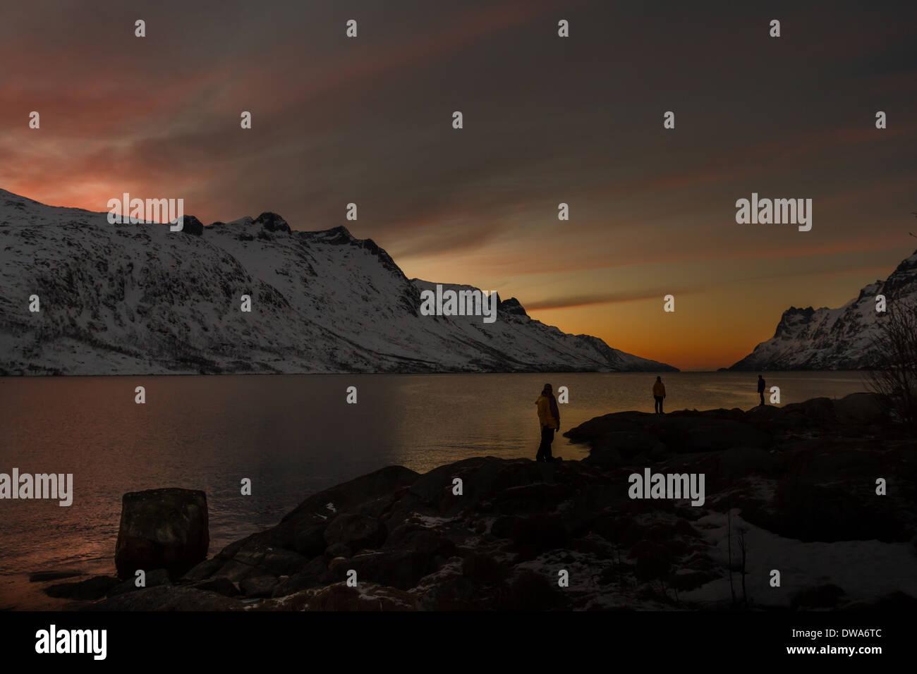 Norwegen Landschaft: 3 Personen gegen die untergehende Sonne auf einer der norwegischen Fjorde an einem Winterabend mit einer Bergkulisse Silhouette Stockbild