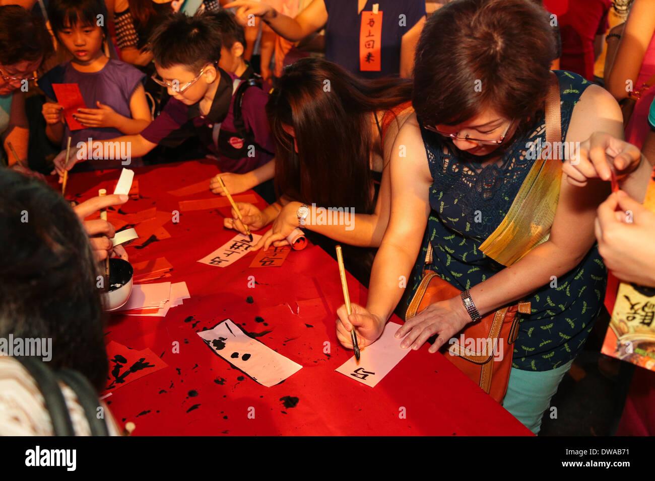 Leute schreiben ihre Wünsche in der chinesischen Kalligraphie in ...
