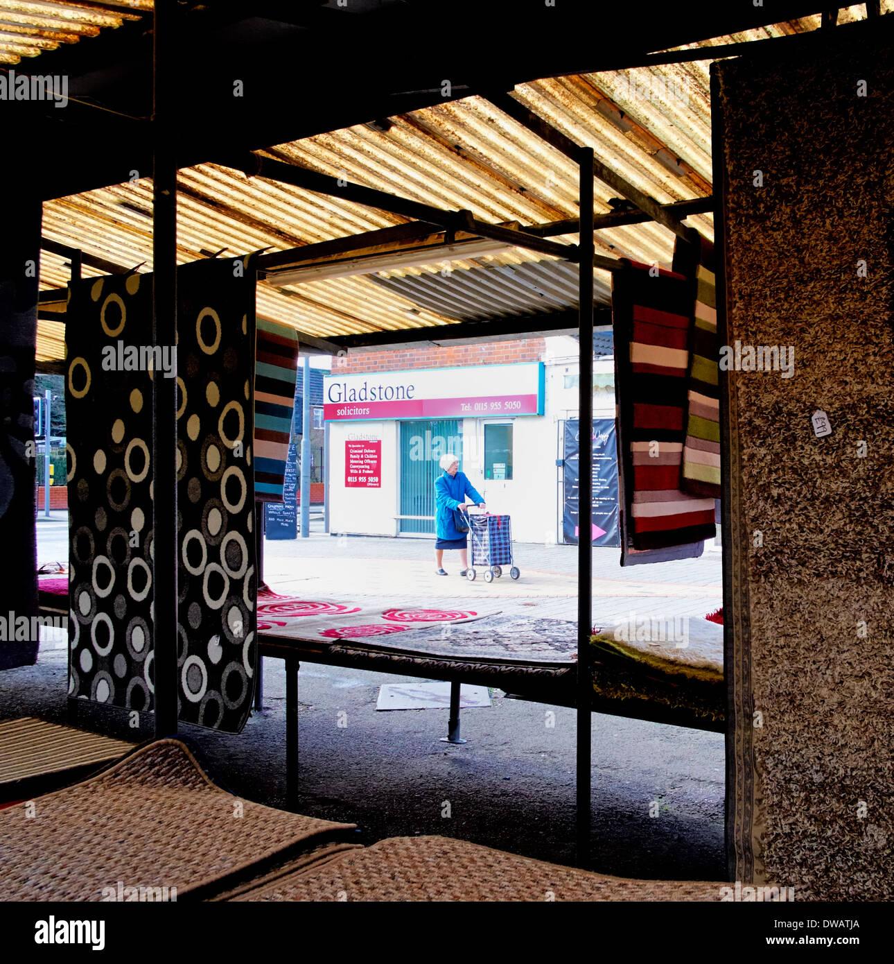 Rentner schieben ein Einkaufswagen, gesehen durch ein outdoor-Markt Teppich stall Arnold Nottingham England uk Stockbild