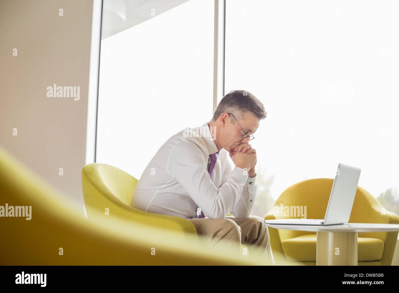 Seitenansicht des ernsthaften Geschäftsmann Blick auf Laptop in der lobby Stockbild