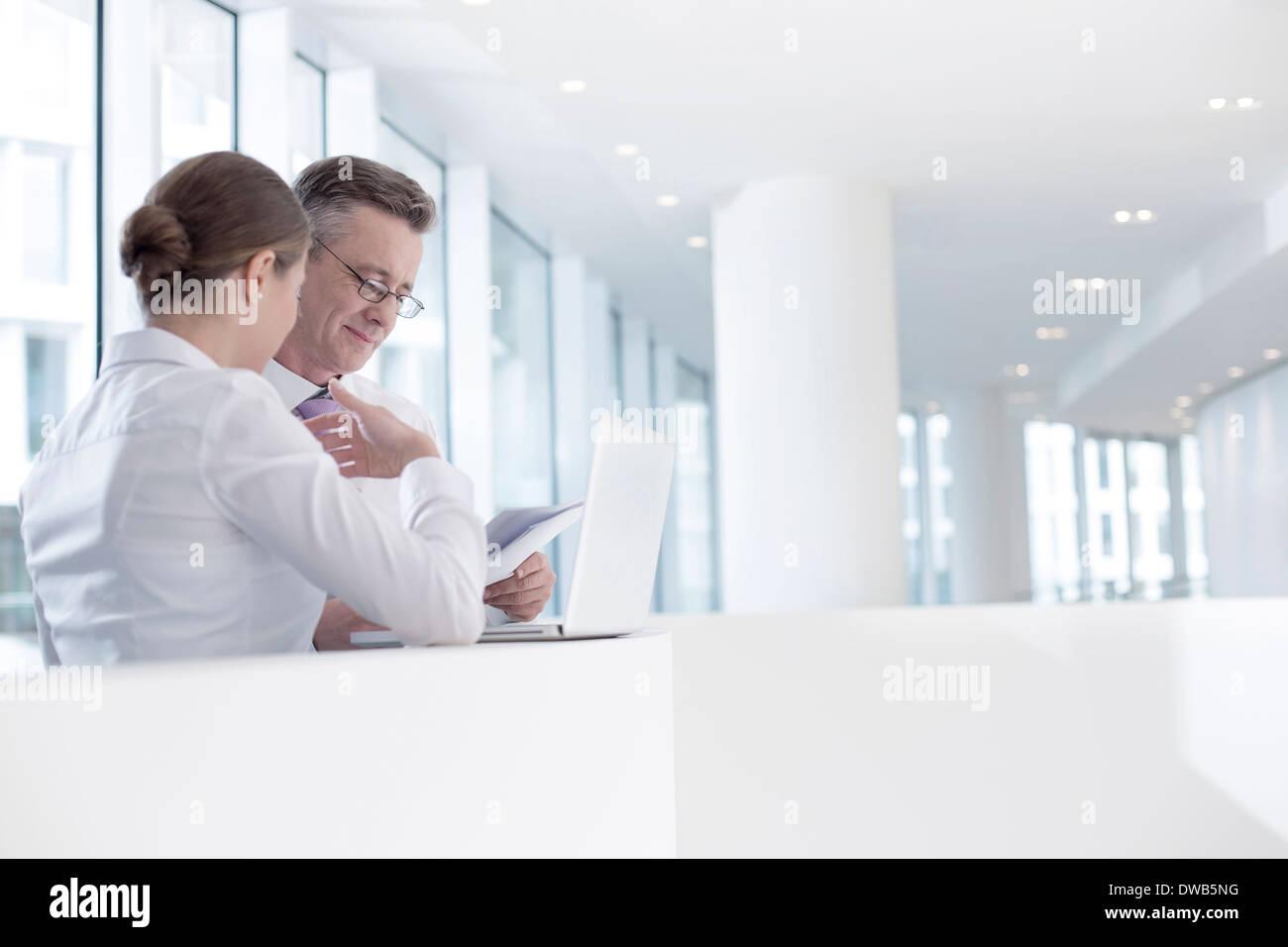 Geschäftsleute, die am Geländer im Büro Stockbild