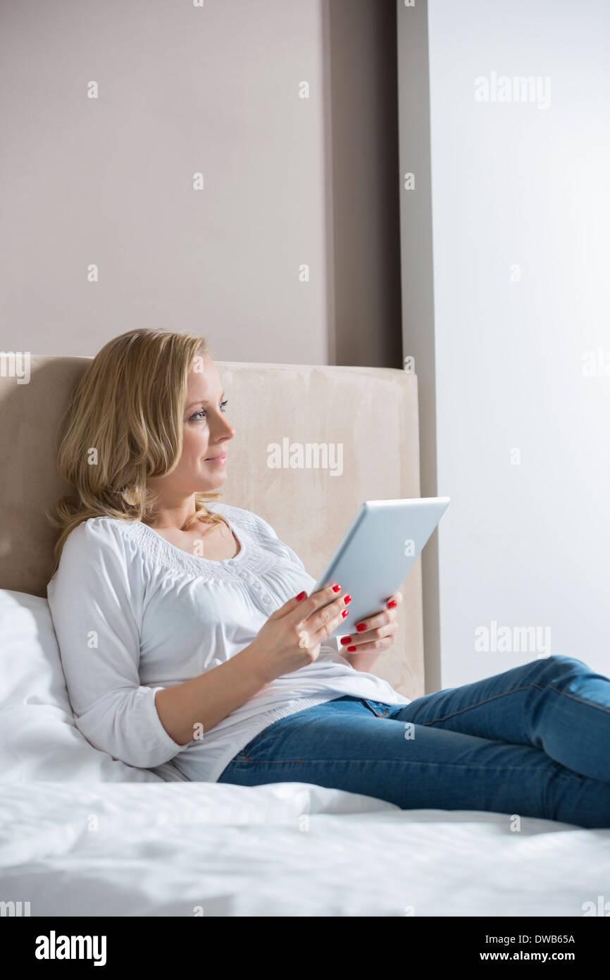 Nachdenklich Mitte Erwachsene Frau mit digital-Tablette im Schlafzimmer Stockbild