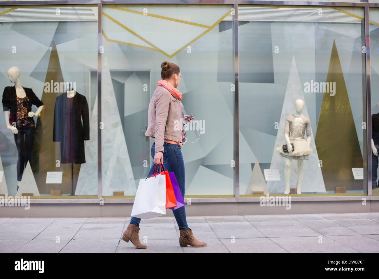Profil-Schuss der jungen Frau mit Einkaufstüten Schaufenster betrachten Stockbild