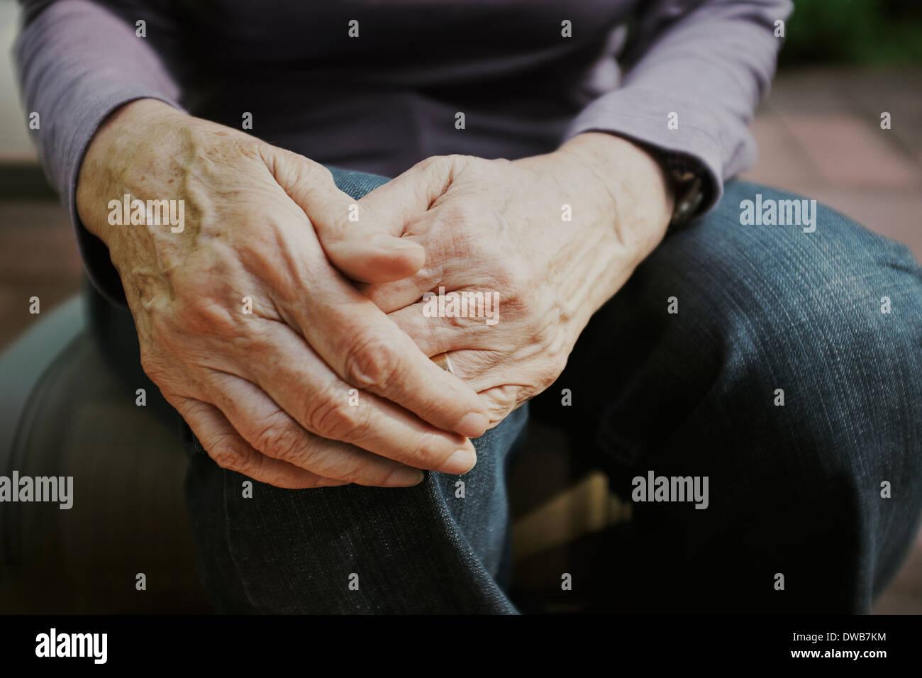 Zugeschnittene Aufnahme senior Frau mit den Händen auf die Knie Stockbild