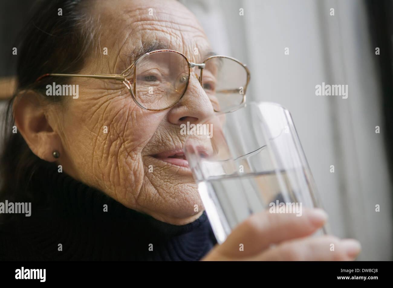 Ältere Frau mit Glas Trinkwasser Stockbild