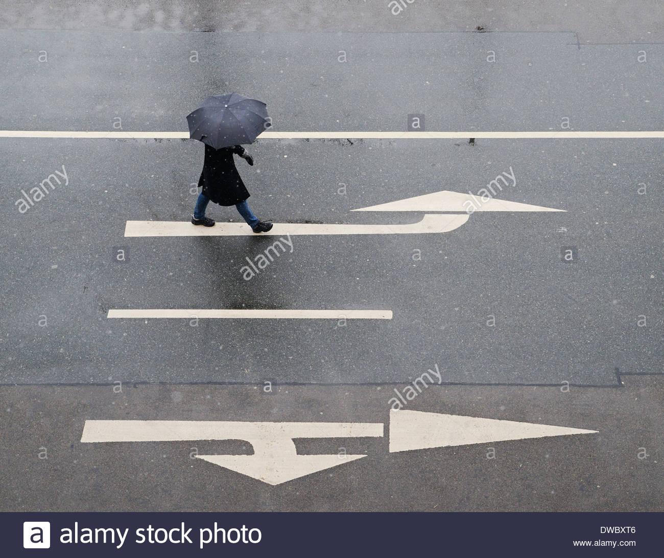 Erhöhte Ansicht von Frau mit Regenschirm zu Fuß unterwegs Stockbild
