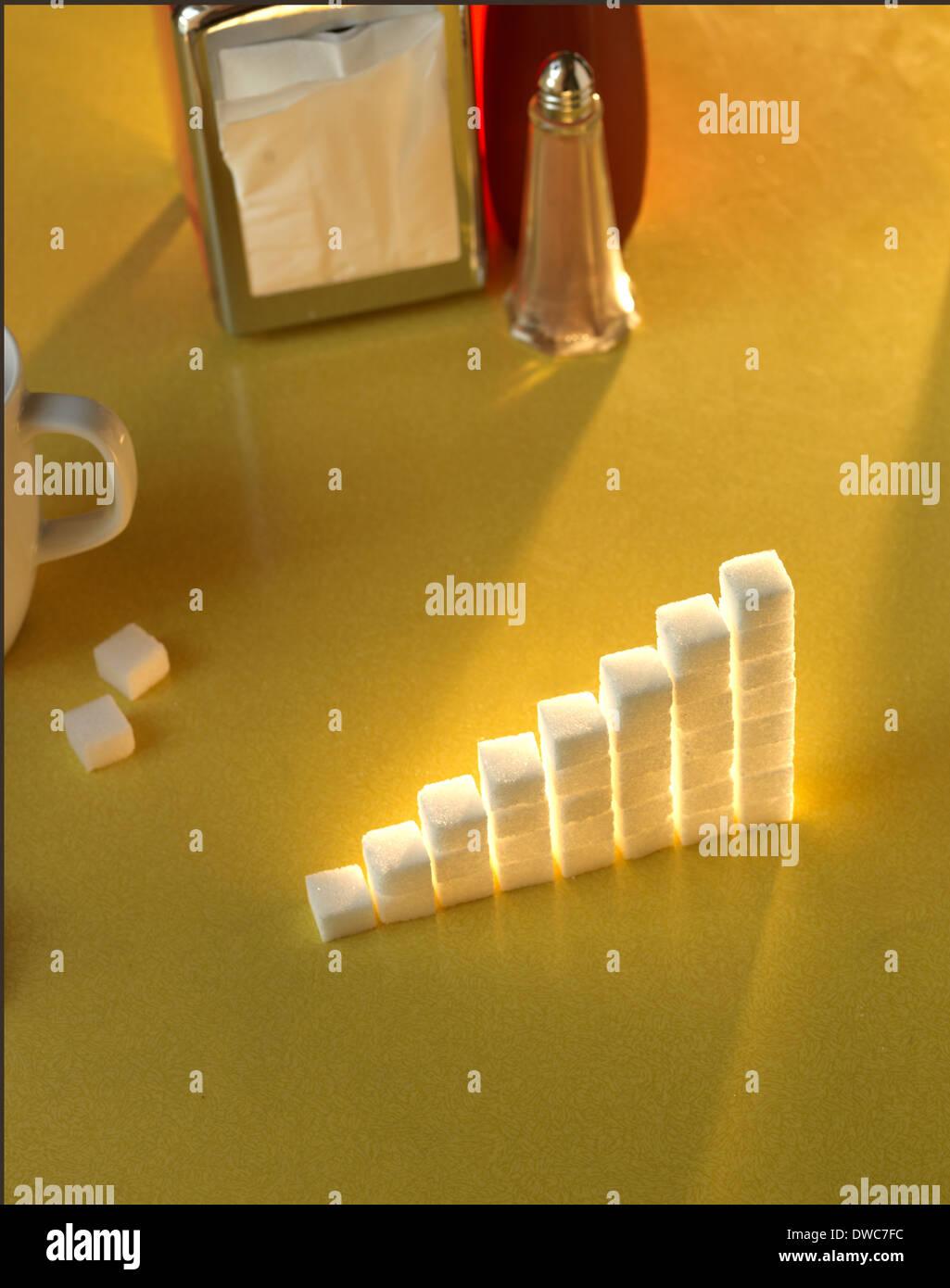 Stapel von Würfelzucker in der Form eines Graphen auf einem gelben Tisch Stockbild