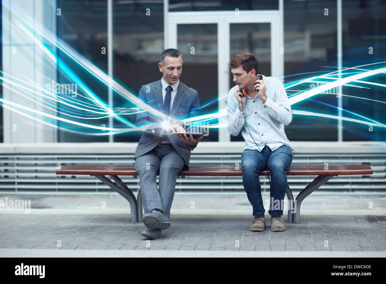 Geschäftsmann und junger Mann gerade digital-Tablette und Wellen der Beleuchtung Stockbild