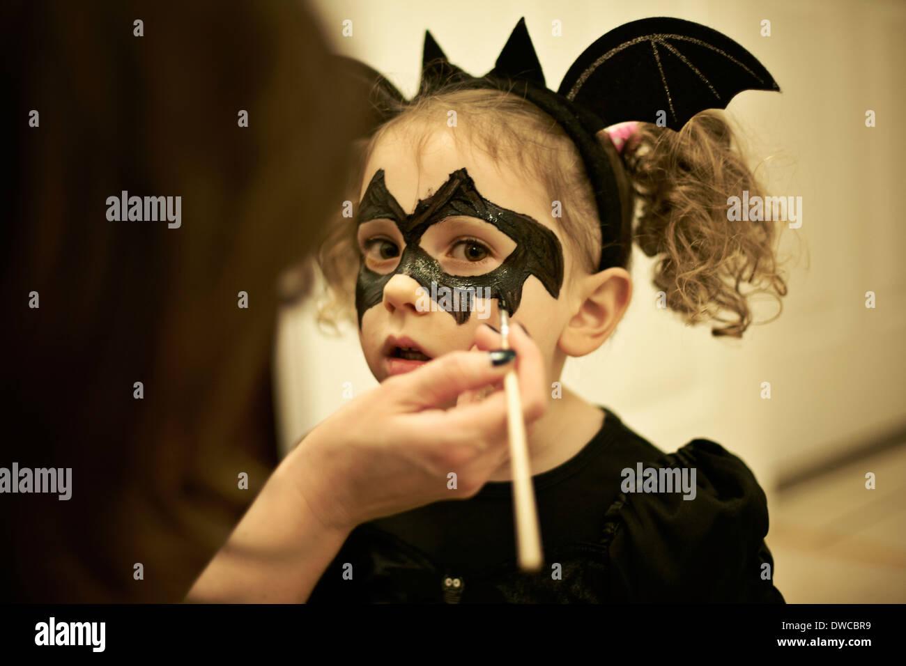 Mutter Malerei Töchter Gesicht für Halloween Fledermaus-Kostüm Stockbild
