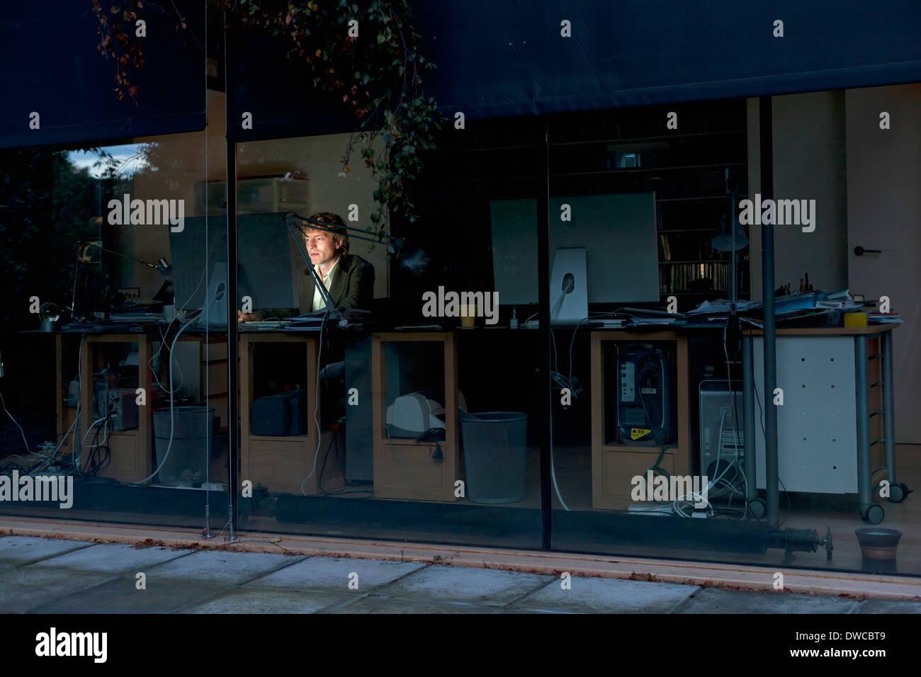Junger Mann zu Hause arbeiten spät am computer Stockfoto