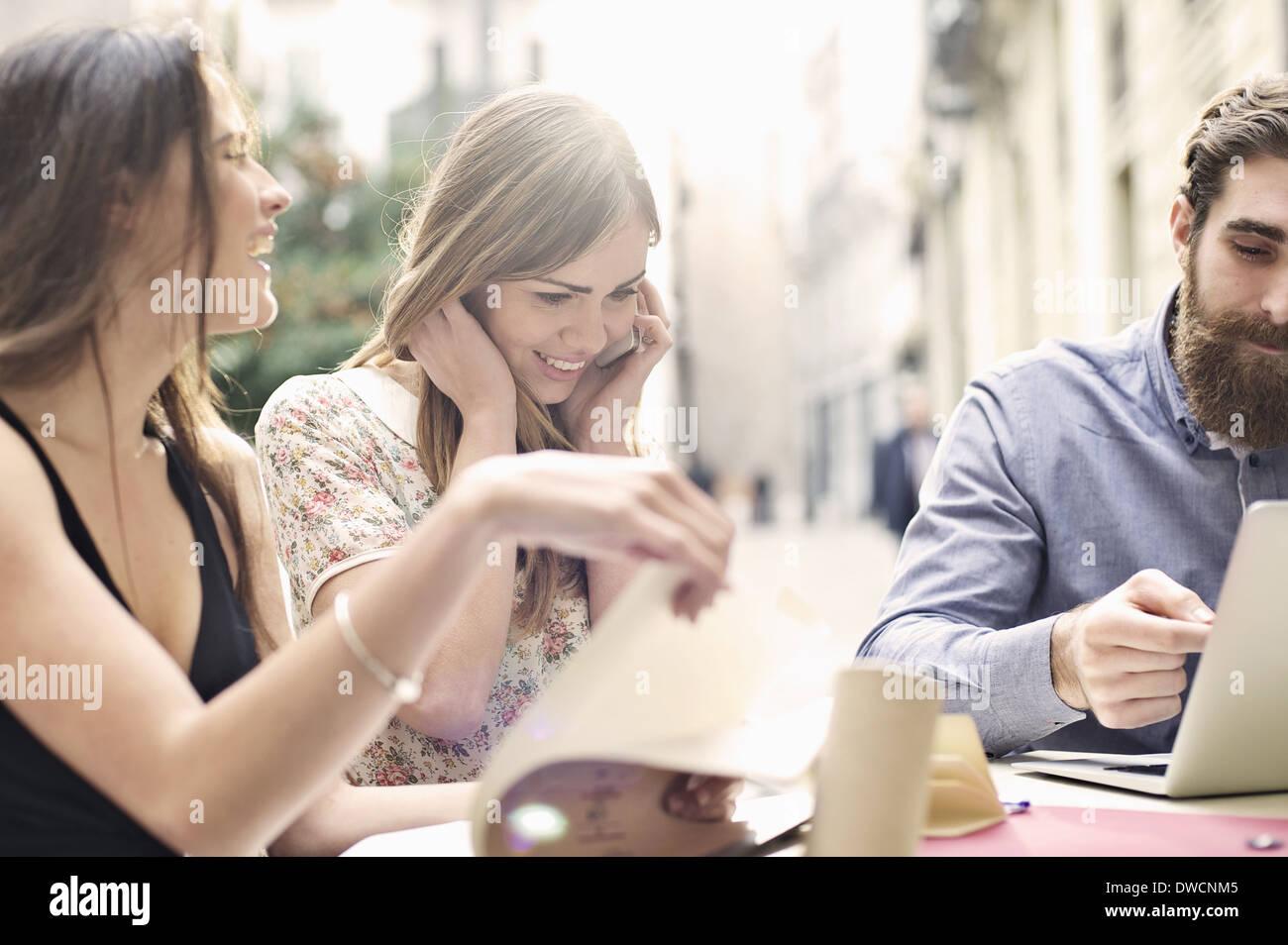 Drei touristische Freunde genießen eine Pause am Bürgersteig Café, Valencia, Spanien Stockbild